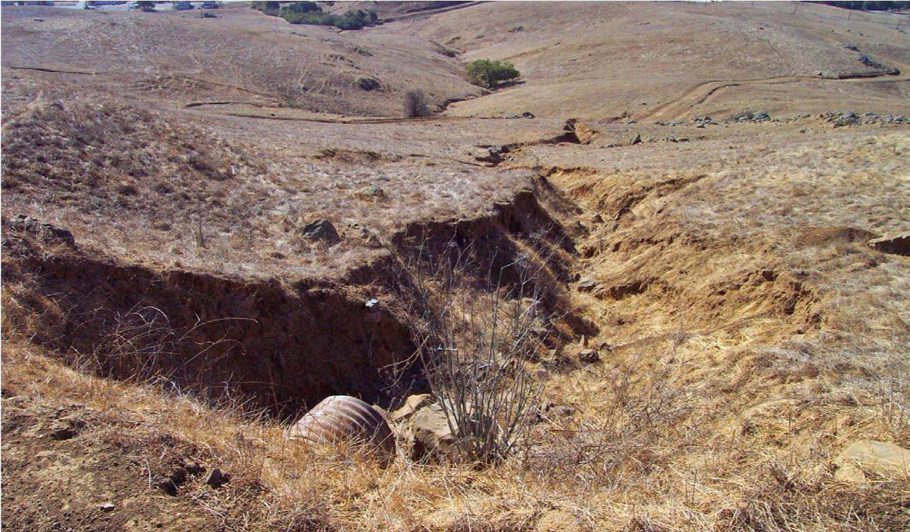 On a brown, grassy landscape, a long, jagged-edged gully is shown at the outlet of a culvert.