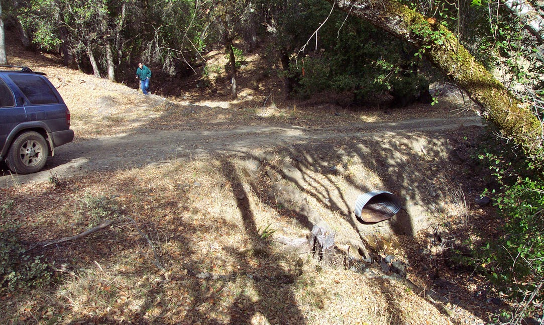 A dirt road has a culvert (that looks squashed) for a stream crossing zone.