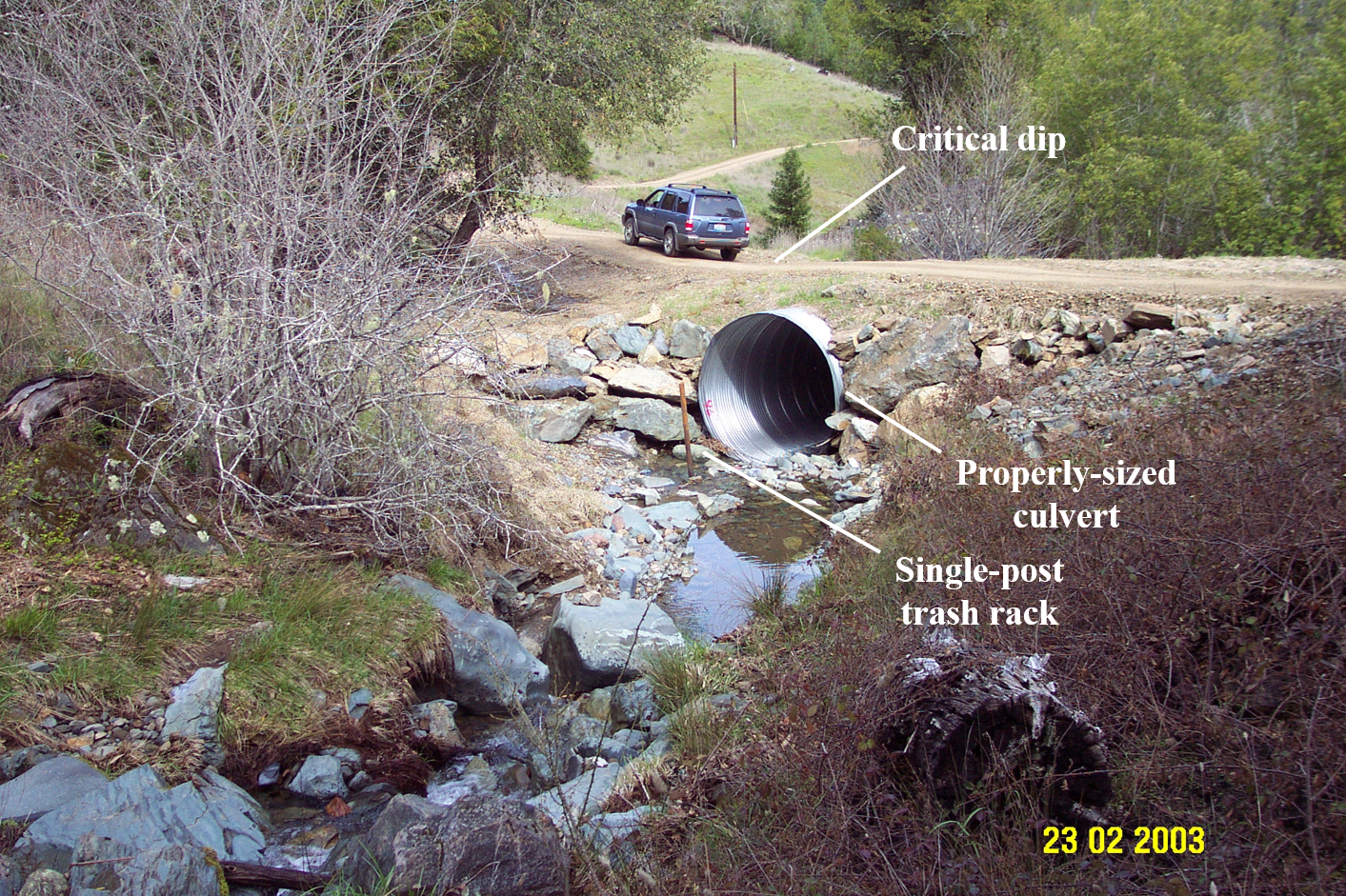 A larger view of a dirt road shows a culvert (with an associated trash rack). About 5-10 feet up from the culvert, a critical dip (a literal dip in the road) has been installed to ensure the stream is not diverted in a storm