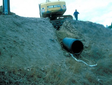 A backhoe and a person are shown with a half-buried culvert, demonstrating the angle of install.