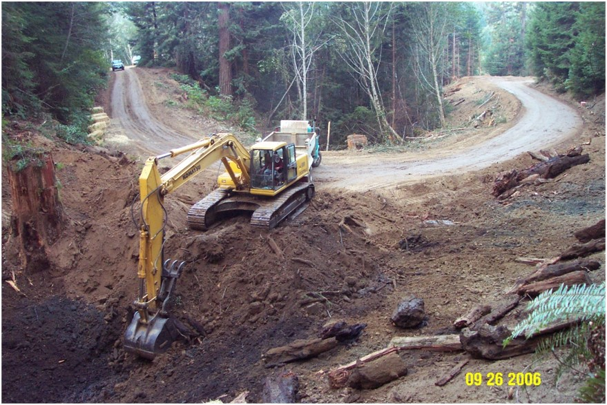 In this image, the same site has been cleared of vegetation. The road surface looks smooth, and a back-hoe is building up the bank on the side of the road.
