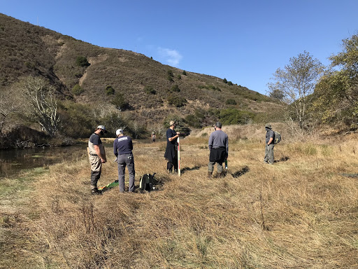 In the same location as the first image, 6 people are gathered, seeming to discuss the landscape. One is dressed in waders and another has a measuring device.
